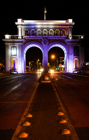 Monument of Los Arcos de Guadalajara, illuminated at night with purple, blue and red lights