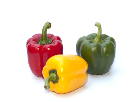 Red, yellow and green bell peppers isolated on the white background photo