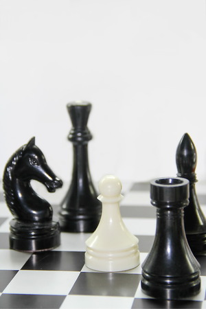 One white pawn among black chess pieces photo