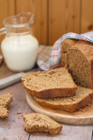 Homemade rye bread and milk on the wooden table photo