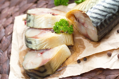 japanese cookery: Smoked fish with vegetables and spices on the wooden table