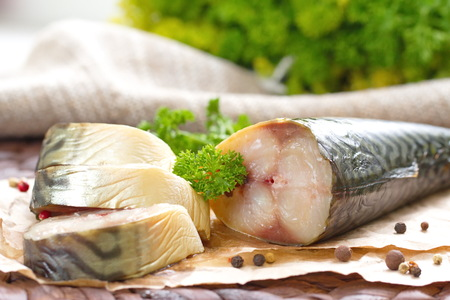 Smoked fish with vegetables and spices on the wooden table