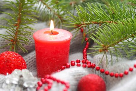 Rote Kerze mit Weihnachtsschmuck