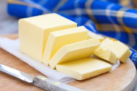 mantequilla: la mantequilla fresca en rodajas sobre la mesa de madera