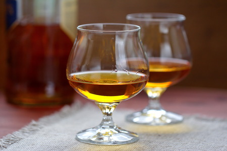 cognac: Glass of cognac on the wooden table Stock Photo