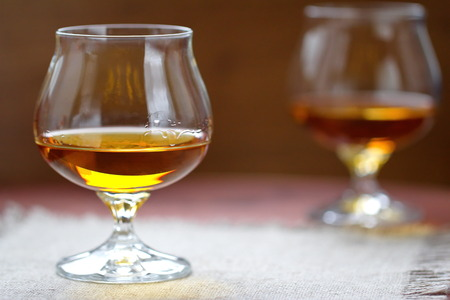 glass table: Glass of cognac on the wooden table Stock Photo