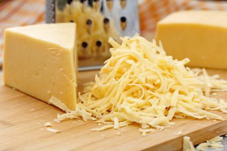 queso rayado: Queso rallado sobre la mesa de madera