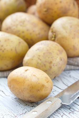 unpeeled: Raw unpeeled potatoes on the table