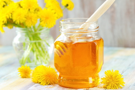 Flower honey in glass jar and dandelions
