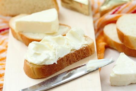 Geschnittenes Brot mit Frischkäse und Butter zum Frühstück Standard-Bild - 57173194