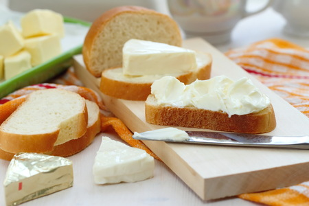 Sliced bread with cream cheese and butter for breakfast Foto de archivo