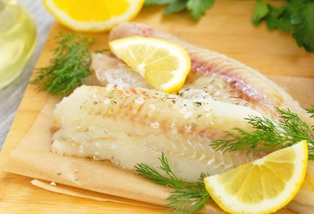 Roher Fisch mit Gewürzen, Zitrone und Gemüse Standard-Bild - 57173267