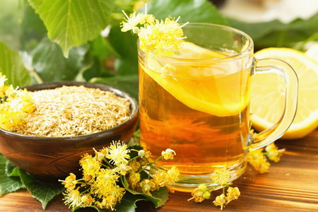 linden flowers: Cup of herbal tea with linden flowers and lemon