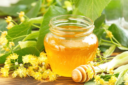 Linden honey in glass jar and linden flowers Stock fotó