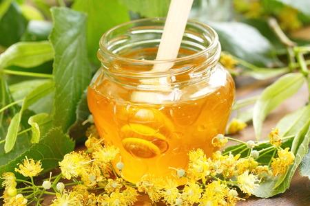 tilo: la miel de tilo en el tarro de cristal y flores de tilo Foto de archivo