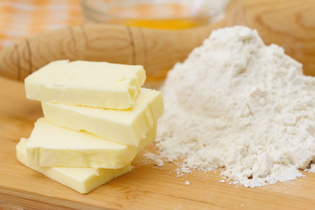 Baking ingredients: butter, eggs and flour on the table