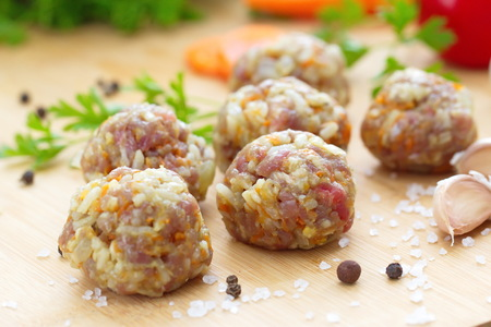 Raw meatballs on a chopping board and ingredients for cooking Stock Photo