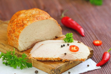 veal sausage: Delicious spicy meat. Spicy meat baked with chili pepper. Piece of baked meat with spices and vegetables on the table. Spicy baked meat prepared for eat. Stock Photo