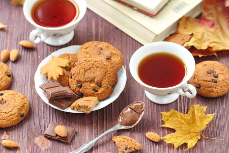 Autumn lifestyle with hot tea, sweets and yellow leaves on the wooden background Stock Photo