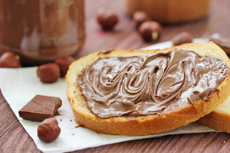 Chocolate nut paste with slices of fresh white bread Standard-Bild