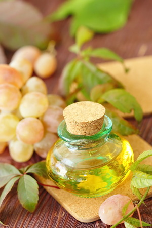 grape seed: Bottle with grape seed essential oil on a wooden table Stock Photo