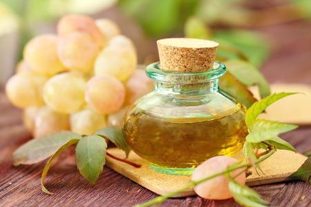 Flasche mit Traubenkern ätherisches Öl auf einem Holztisch Standard-Bild - 64746984