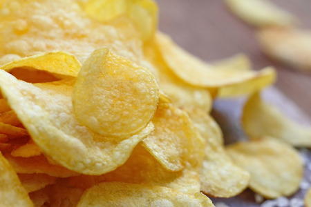 Salted potato chips on the table. Fast food. Stock Photo