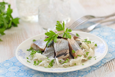 Delicious herring fillet with oil, marinated onion and fresh parsley