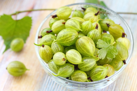 Ripe gooseberries in a bowl on the wooden table