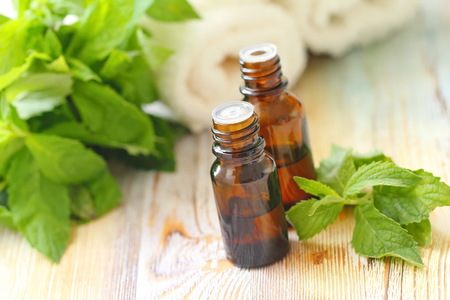 Essential aroma oil with mint on wooden background
