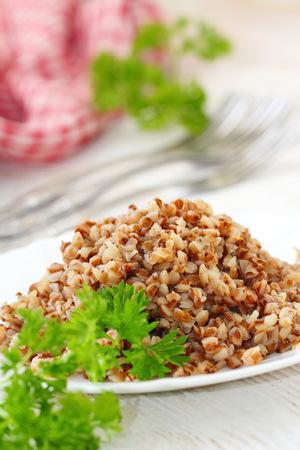 Buckwheat porridge on a plate and fresh vegetables Lizenzfreie Bilder