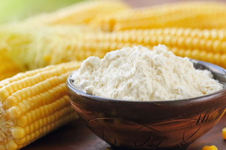 Corn flour in a bowl and corn cob on the table