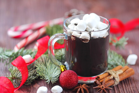 Cup of dark hot chocolate with marshmallows on a wooden table with christmas decoration