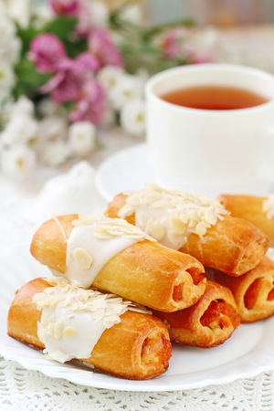 Delicious roll with sweet cream, almond nuts and apricot jam