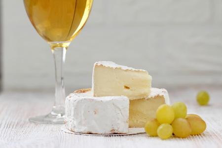 Cheese, fresh grape and white wine in glass