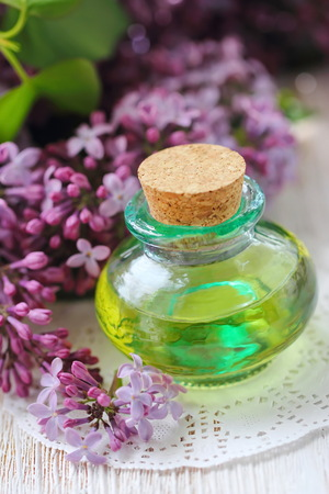 Essential aroma oil with lilac on wooden background