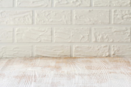 White wooden table with a brick wall as a background. Mockup