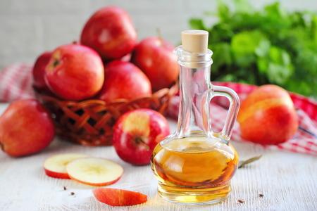 Appelazijn. Fles appelazijn op houten achtergrond. Gezond eten.