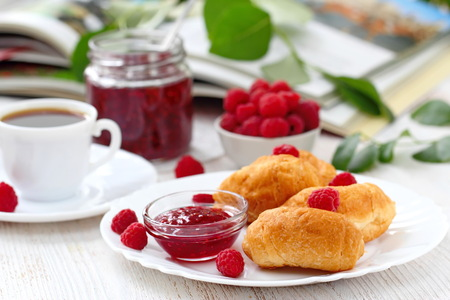 Sweet buns on a white plate with ripe raspberries and jam Foto de archivo