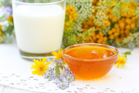 Glass of milk and fresh honey in bowl with flowers background Archivio Fotografico