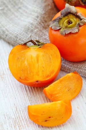 Ripe persimmon fruit on wooden table ready for eat