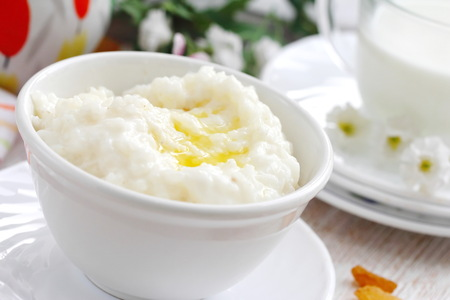 Sweet rice porridge with fresh butter and mug of milk Stock fotó