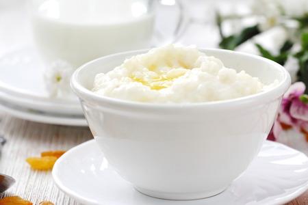Sweet rice porridge with fresh butter and mug of milk Stock Photo