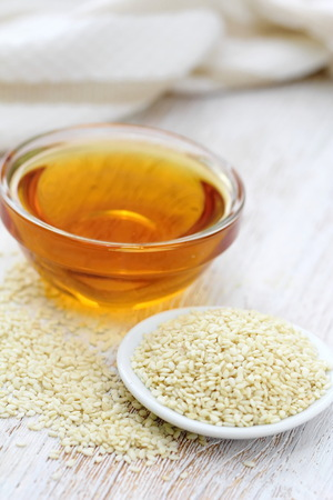 Sesame oil in glass and sesame seeds on the table Stock fotó