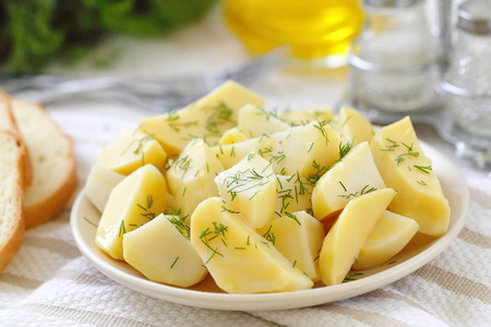 Boiled potatoes with fresh greens and oil ready for eat Banco de Imagens