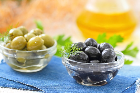 Green and black olives in glass bowls and olive oil on a table Stock fotó