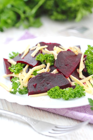 Salad with beet, cheese and fresh greens served witn oil and balsamic vinegar