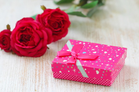 Fresh red roses and gift box on wooden table. St. Valentines Day concept. Stockfoto