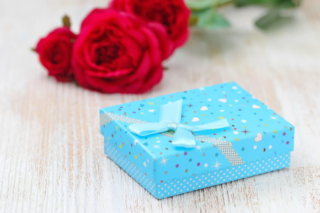 Fresh red roses and gift box on wooden table. St. Valentines Day concept. Stock fotó
