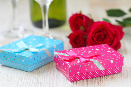 Fresh red roses and gift boxes on wooden table. St. Valentines Day concept.